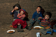 (MODEL RELEASED IMAGE). The Ayme family sits on the dirt floor of their kitchen and eats soup and empanadas for breakfast in Tingo, Ecuador. (Supporting image from the project Hungry Planet: What the World Eats.)