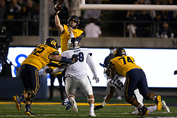 California quarterback Chase Garbers (7) leaves his feet to pass over Nevada defensive tackle Dom Peterson (99) during the third quarter of an NCAA college football game, Saturday, Sept. 4, 2021, in Berkeley, Calif. (AP Photo/D. Ross Cameron)