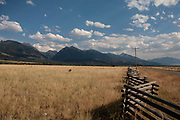 Clouds in Big Sky country. White clouds in the blue sky above Black Mountain in Paradise Valley near Livingstone, Montana. With grass bleached in the sun, this ranch land is the driest it will be all year.