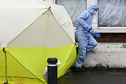 © Licensed to London News Pictures. 09/04/2019. London, UK. A forensic officer investigates around the police tent on Church Road, Manor Park, East London where a man in his 20s was shot and stabbed to death on Monday 8 April 2019. Police were called around 9.30pm and the man was was found with knife and gunshot wounds. The victim was pronounced dead at the scene.  Photo credit: Dinendra Haria/LNP