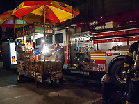 Street vendor who practices extreme fire safety; Fifth Avenue, New York.