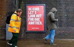 © Licensed to London News Pictures. 30/03/2020. London, UK. People observe social distancing as they walk past a 'Be Kind. Let's Look out for one Another.' sign in north London as  coronavirus lockdown continues.  Photo credit: Dinendra Haria/LNP