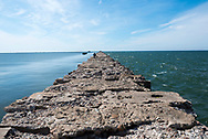 Liepaja, Latvia - August 22, 2015: A man walks on a jetty  which extends far out into the Baltic sea at Karosta, a former Soviet naval compound on the northern side of Liepaja, Latvia. The calm waters of the harbor are on the left; the rough waters on the right.