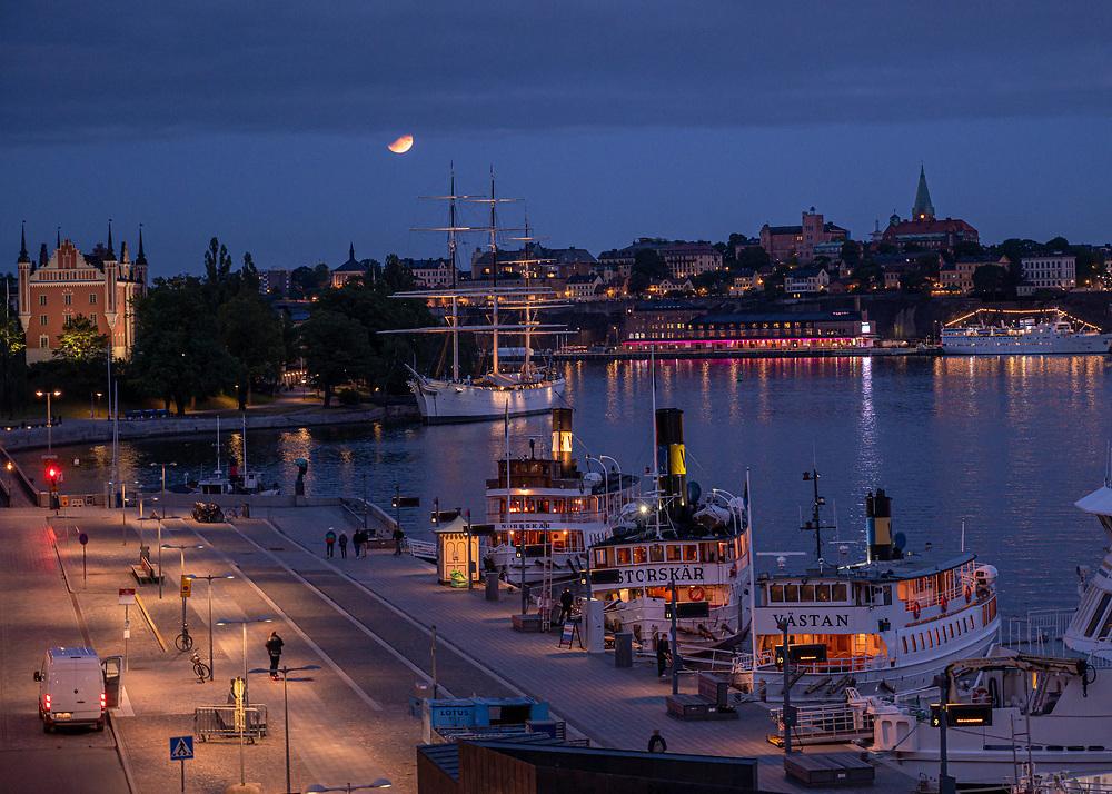 Stockholm, Sweden -- July 17, 2019. A half-moon descends over Stockholm that is lit up for the night.