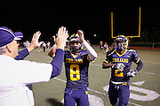 Milpitas High School head coach Kelly King gives David Kruskamp (8) and teammates high fives after beating Sacred Heart Cathedral 28-21 at Milpitas High School in Milpitas, California, on September 20, 2013. (Stan Olszewski/SOSKIphoto)