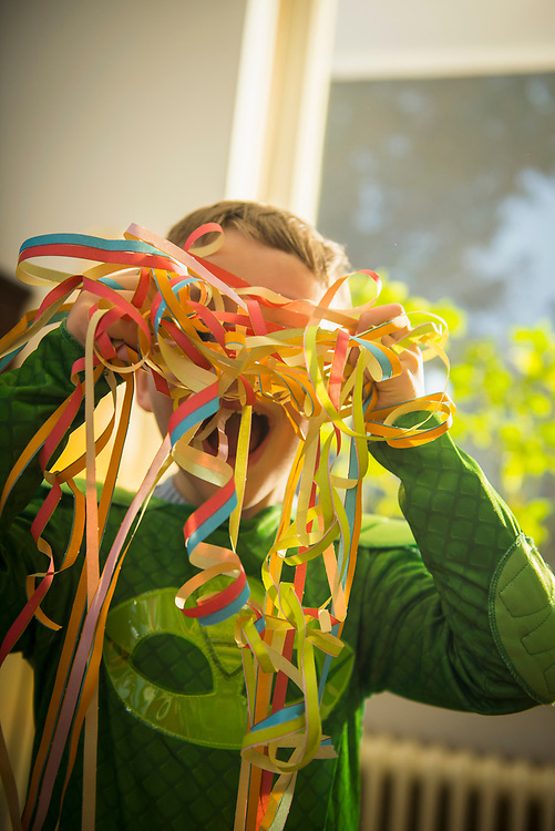 Little boy with paper streamers in front of his face