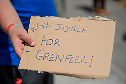"© Licensed to London News Pictures. 17/06/2017. London, UK. A man hols a sign reading ""justice for Grenfell"" outside Grenfell tower block in west London earlier this week. The blaze engulfed the 27-storey building killing 12 - with 34 people still in hospital, 18 of whom are in critical condition. The fire brigade say that they don't expect to find anyone else alive. Photo credit: Ben Cawthra/LNP"
