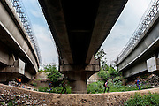 26th March 2014, Shakarpur, New Delhi, India. Children walk underneath the Delhi Metro line in the morning on their way to attend a makeshift school under a metro bridge near the Yamuna Bank Metro station in Shakarpur, New Delhi, India on the 26th March 2014<br /> <br /> Rajesh Kumar Sharma (born 01/02/1970), started this makeshift school in 2011. Six mornings a week he teaches underprivileged children for three hours while his younger brother replaces him at his general store in Shakarpur. His students are children of labourers, rickshaw-pullers and farm workers. This is the 3rd site he has used to teach under privileged children in the city, he began in 1997. <br /> <br /> PHOTOGRAPH BY AND COPYRIGHT OF SIMON DE TREY-WHITE<br /> + 91 98103 99809<br /> email: simon@simondetreywhite.com<br /> photographer in delhi<br /> journalist