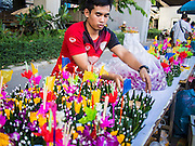 "17 NOVEMBER 2013 - BANGKOK, THAILAND:  A man makes krathongs to sell to temple goers near Wat Yannawa on Loy Krathong. Loy Krathong (also written as Loi Krathong) is celebrated annually throughout Thailand and certain parts of Laos and Burma (in Shan State). The name could be translated ""Floating Crown"" or ""Floating Decoration"" and comes from the tradition of making buoyant decorations which are then floated on a river. Loi Krathong takes place on the evening of the full moon of the 12th month in the traditional and they do this all evening on the 12th month Thai lunar calendar. In the western calendar this usually falls in November. The candle venerates the Buddha with light, while the krathong's floating symbolizes letting go of all one's hatred, anger, and defilements      PHOTO BY JACK KURTZ"