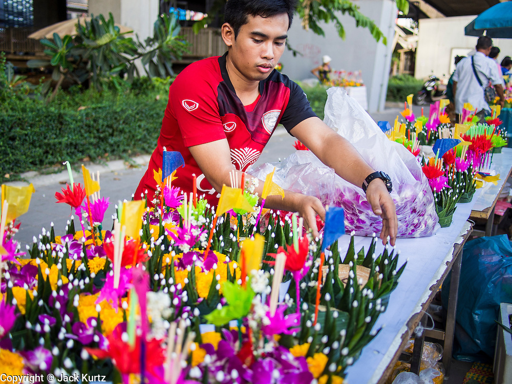 """17 NOVEMBER 2013 - BANGKOK, THAILAND:  A man makes krathongs to sell to temple goers near Wat Yannawa on Loy Krathong. Loy Krathong (also written as Loi Krathong) is celebrated annually throughout Thailand and certain parts of Laos and Burma (in Shan State). The name could be translated """"Floating Crown"""" or """"Floating Decoration"""" and comes from the tradition of making buoyant decorations which are then floated on a river. Loi Krathong takes place on the evening of the full moon of the 12th month in the traditional and they do this all evening on the 12th month Thai lunar calendar. In the western calendar this usually falls in November. The candle venerates the Buddha with light, while the krathong's floating symbolizes letting go of all one's hatred, anger, and defilements      PHOTO BY JACK KURTZ"""