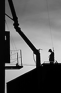 An employee of the Davenport Union Warehouse Co guides the loader as it fills a hopper car with grain.