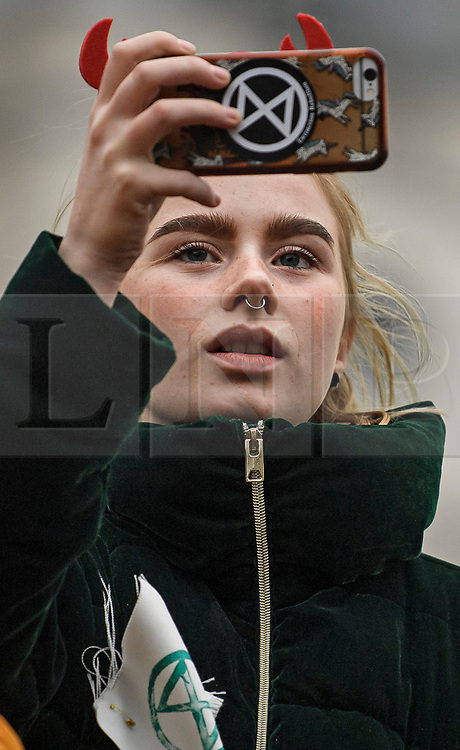 © Licensed to London News Pictures. 07/10/2019. London, UK. An Extinction Rebellion activist takes a picture while sat on a wooden structure in Trafalgar Square, Westminster. Activists will converge on Westminster blockading roads in the area for at least two weeks calling on government departments to 'Tell the Truth' about what they are doing to tackle the Emergency. Photo credit: Ben Cawthra/LNP
