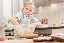 Girl mixing batter in bowl for cookies, smiling, portrait