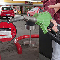 Female driver fuels up her car at a gas station in Budapest, Hungary on June 24, 2009. ATTILA VOLGYI