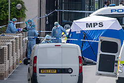 © Licensed to London News Pictures. 11/06/2021. London, UK. Forensic investigators gather around a tent at the scene of a fatal stabbing in Hayes, Metropolitan Police were called at 08:34BST to a report of a fight on Blyth Road in Hayes. Emergency services, including London Ambulance Service and London's Air Ambulance, attended the location and found a 15-year-old boy suffering from multiple stab wounds. The teenager died at the scene. Photo credit: Peter Manning/LNP