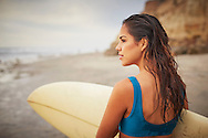A beautiful young woman holds a surfboard while standing on the beach in San Diego, California.