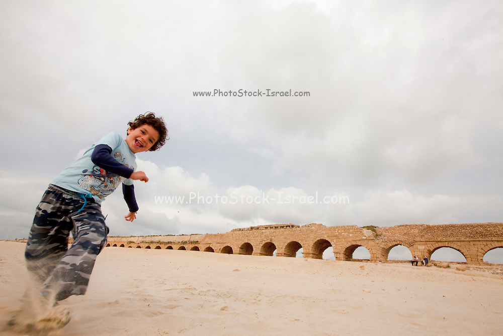 Child plays in the sand the Roman aqueduct in the background