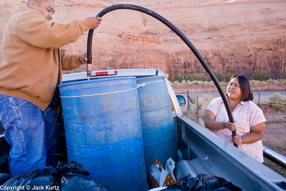22 OCTOBER 2007 -- MONUMENT VALLEY, UT: ORLANDO CLY and his wife, MARIE CLY, Navajo Indians living on the Navajo Reservation in northern Arizona, fill 50 gallon barrels with potable water at the well at Goulding's Trading Post near Monument Valley, UT. The well at Goulding's was first dug by Seventh Day Adventists missionaries and is the only source of clean, free water for miles around. More than 30 percent of the homes on the Navajo Nation, about the size of West Virginia and the largest Indian reservation in the US, don't have indoor plumbing or a regular supply of domestic water. Many of these homes have to either buy water from commercial vendors or haul water from public wells. A Federal study showed that the total cost of hauling water was about $113 per 1,000 gallons. A Phoenix household, in comparison, pays just $5 a month for up to 7,400 gallons of water. The lack of water on the reservation means the Navajo are among the most miserly users of water in the United States. Families that have to buy or haul water use only about 15 gallons of water per day per person. In Phoenix, by comparison, the average water use is about 170 gallons per day.  Photo by Jack Kurtz