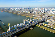 Nederland, Zuid-Holland, Rotterdam, 18-02-2015; Botlek, Hartelkanaal met Hartelkering (stormvloedkering). De kering, onderdeel van de Deltawerken, vormt samen met de Maeslantkering de Europoortkering en beschermt Rotterdam en achterland bij extreme waterstanden.<br /> In de achtergrond  Esso-olieraffinaderij (ExxonMobil).<br /> Storm surge barrier Hartelkering in the Hartel canal. Together with the greater nearby Maeslant barrier (in the New Waterway), the barrier proyect nearby Rotterdam and its hinterland.<br /> luchtfoto (toeslag op standard tarieven);<br /> aerial photo (additional fee required);<br /> copyright foto/photo Siebe Swart