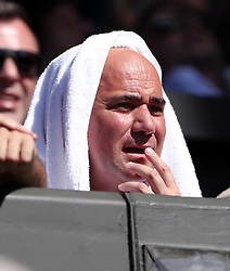 Andre Agassi uses a towel to shield himself from the sun on day six of the Wimbledon Championships at The All England Lawn Tennis and Croquet Club, Wimbledon.