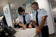 Male and female pilots examine flight data and documents in the British Airways Crew Report Centre at Heathrow Airport's T5