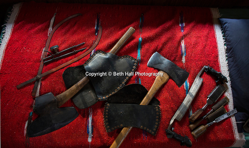 Antique hand tools used for log work lay on a bed at the home of Robert Runyon in Sugar Tree Hollow in Winslow, Arkansas, for Out Here Magazine. Photo by Beth Hall