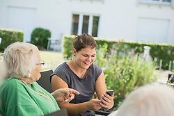 Grandmother and granddaughter discussing over smartphone, Bavaria, Germany