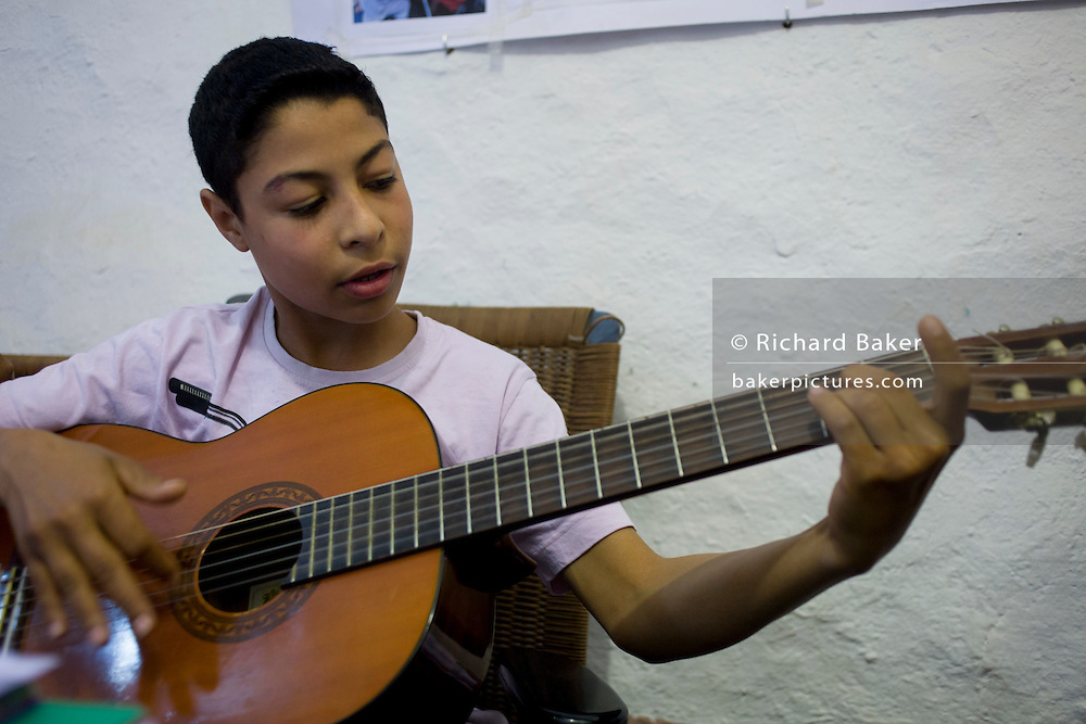 A young Egyptian boy plays an acoustic guitar at the American-sponsored Theban Mapping Project Library on the West Bank of Luxor, Nile Valley, Egypt. He has been playing for only three months and can already play a variety of chords and even recite the theme of the film, Titanic. The Theban Mapping Project's goal is to enable local people to have a place where they can read and learn. The organisation is run by American Egyptologist Dr Kent Weeks who is committed to the original goal of accurately documenting the archaeological heritage of Thebes