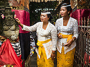 19 JULY 2016 - TAMPAKSIRING, GIANYAR, BALI, INDONESIA: Women watch the ceremony on the first day of a ceremony to honor the anniversary Pura Agung temple, one of the most important Hindu temples on Bali. This year's ceremony is the most important in years because it falls on the 50 year cycle of the temple's founding. This year's ceremony lasts for 11 days.      PHOTO BY JACK KURTZ