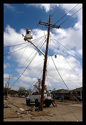 4th Oct, 2005. Hurricane Katrina aftermath, New Orleans, Louisiana. Private contractor telephone and power engineers work to restore services amidst the smashed homes in the Arabi neighbourhood.