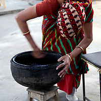 Asia, India, Jaipur. Indian woman cleaning a pot.