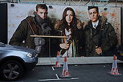 Three Superdry fashion store models on a large hoarding with three traffic parking cones in a London street.