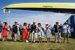 © Licensed to London News Pictures. 04/07/2018. Henley-on-Thames, UK. Family and friends of a rowing team watch as a team takes their boat to the water on day one of the Henley Royal Regatta, set on the River Thames by the town of Henley-on-Thames in England. Established in 1839, the five day international rowing event, raced over a course of 2,112 meters (1 mile 550 yards), is considered an important part of the English social season. Photo credit: Ben Cawthra/LNP