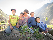 Taking a break from digging potatoes in her field, a Wakhi woman poses with her family.