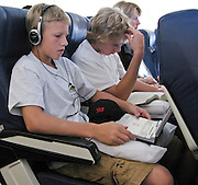 27 JULY 2007 -- PHILADELPHIA, PA: Children watch movies on portable DVD players and read on a transatlantic flight between Philadelphia, PA, and Zurich, Switzerland.  PHOTO BY JACK KURTZ