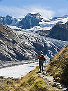A hiker walks along the Morteratsch Glacier in the Bernina Range, Engadine, Switzerland, the Alps, Europe. Pers Glacier flows from Piz Palü (3901 meters or 12,799  feet) into the Morteratsch Glacier (Romansh: Vadret da Morteratsch) in the Bernina massif, in Upper Engadine. A favorite walk is from Morteratsch (second train stop from Pontresina towards Bernina Pass) to Refuge Boval, which has a restaurant and overnight lodging. The trail is well graded 5 or 6 miles round trip with 2700 feet gain. Return via lower trail for partial loop. The Swiss valley of Engadine translates as the garden of the En (or Inn) River (Engadin in German, Engiadina in Romansh, Engadina in Italian). Published in Wilderness Travel Catalog of Adventures 2013.