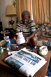 7th Oct, 2005.  New Orleans, Louisiana. Hurricane Katrina aftermath.  81 year old Rosella McKoy collects pennies from a piggy bank at her home in the projects which was miraculously  spared by the floods. A copy of the last full local newspaper lies on the table with the headline Katrina Takes Aim, published on Sunday 28th August, the day before the storm hit.<br /> Photo; ©Charlie Varley/varleypix.com