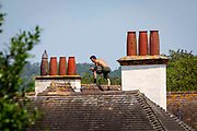 A male roofer walks along the peak of a house roof top on the 21st of July 2021 in Folkestone, Kent, United Kingdom. Roofing is one of the most dangerous professions, some roofers in the UK still work without the correct safety equipment.