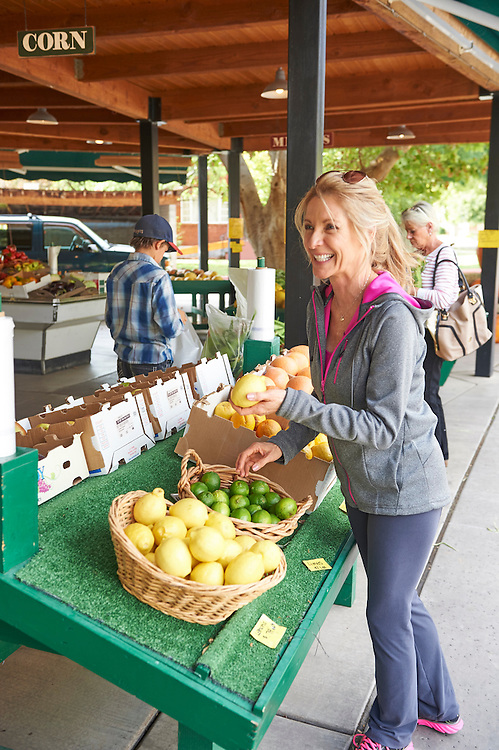 casual dressed blonde woman shopping in an outdoor farmers market in southern Utah.