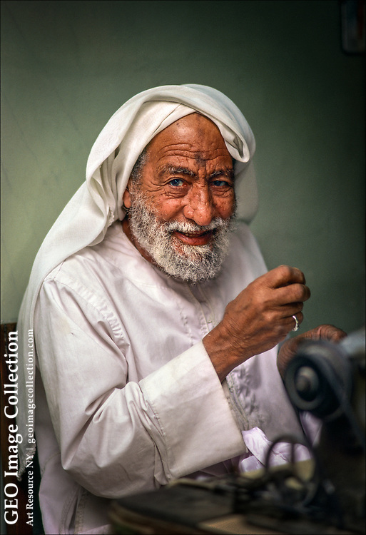 An elderly tailor in the Persian Gulf kingdom of Bahrain uses a foot-powered sewing machine to make custom garments.