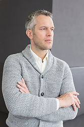 Businessman standing with arms crossed, looking away