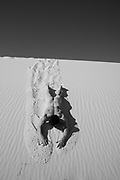 nude muscular man sliding down a sand dune