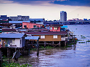 "20 JUNE 2017 - BANGKOK, THAILAND:   Riverfront homes in a community along the Chao Phraya River south of Krung Thon Bridge. This is one of the first parts of the riverbank that is scheduled to be redeveloped. The communities along the river don't know what's going to happen when the redevelopment starts. The Chao Phraya promenade is development project of parks, walkways and recreational areas on the Chao Phraya River between Pin Klao and Phra Nang Klao Bridges. The 14 kilometer long promenade will cost approximately 14 billion Baht (407 million US Dollars). The project involves the forced eviction of more than 200 communities of people who live along the river, a dozen riverfront  temples, several schools, and privately-owned piers on both sides of the Chao Phraya River. Construction is scheduled on the project is scheduled to start in early 2016. There has been very little public input on the planned redevelopment. The Thai government is also cracking down on homes built over the river, such homes are said to be in violation of the ""Navigation in Thai Waters Act."" Owners face fines and the possibility that their homes will be torn down.              PHOTO BY JACK KURTZ"