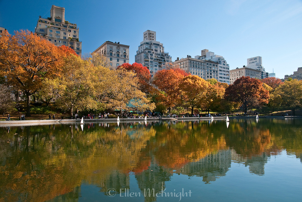 Autumn reflections of Fifth Avenue buildings and trees on the Model Boat Pond in Central Park, New York City
