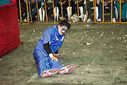 Male wrestler looking injured on floor, out of ring with popcorn on the floor in background. Lucha Libre wrestling origniated in Mexico, but is popular in other latin Amercian countries, including in La Paz / El Alto, Bolivia. Male and female fighters participate in the theatrical staged fights to an adoring crowd of locals and foreigners alike.