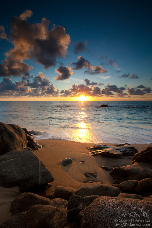 The sun sets over the Pacific Ocean in this view from a rocky beach near Sayulita, Mexico.
