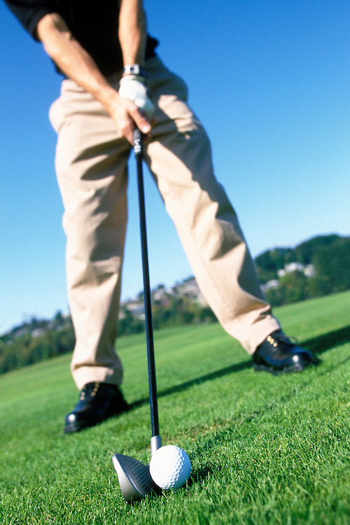 Low angle view of a man lining up a golf shot from the tee.