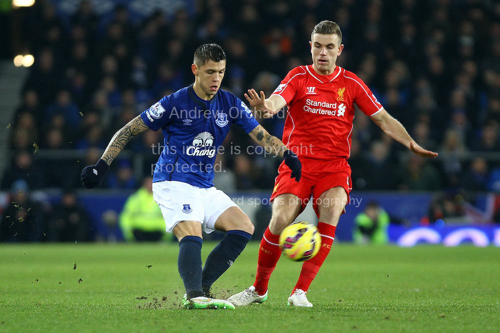 Muhamed Besic of Everton passes the ball under pressure from Jordan Henderson of Liverpool. Barclays Premier league match, Everton v Liverpool at Goodison Park in Liverpool, Merseyside on Saturday 7th February 2015<br /> pic by Chris Stading, Andrew Orchard sports photography.