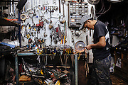 A young man sharpens a knife in a motorcycles workshop in Ciudad Nezahualcoyotl, March 30, 2011.