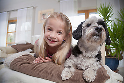 Girl with dog in a living room, Bavaria, Germany